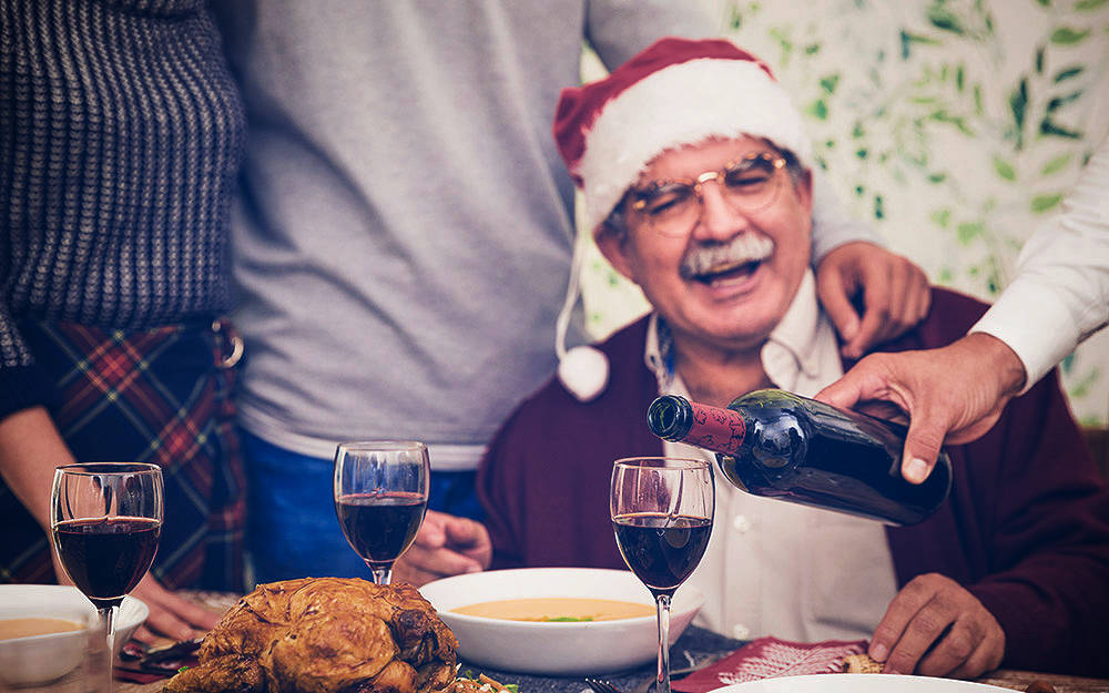 Happy grandfather with glass of wine